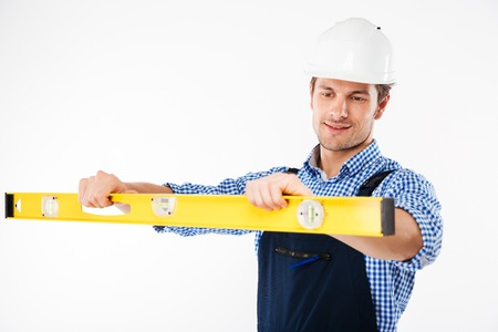 Portrait of a concentrated young worker in overalls using level tool isolated on a white background