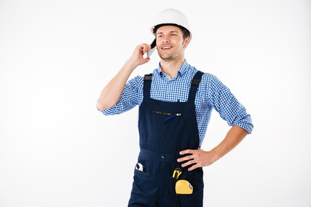 Handsome young builder in overall talking on mobile phone isolated on a white background