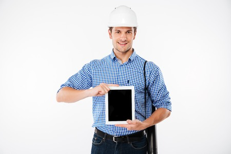 worker working: Cheerful young man builder in hard hat holding and showing blank screen tablet
