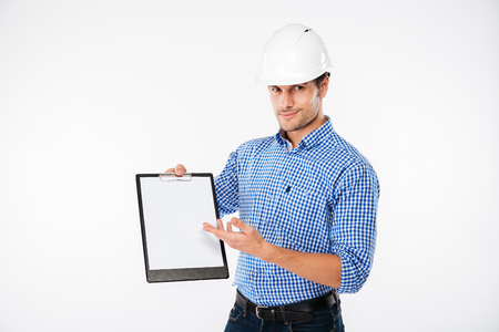 Happy young man building engineer in hard hat holding and pointing on blank clipboard Stock Photo