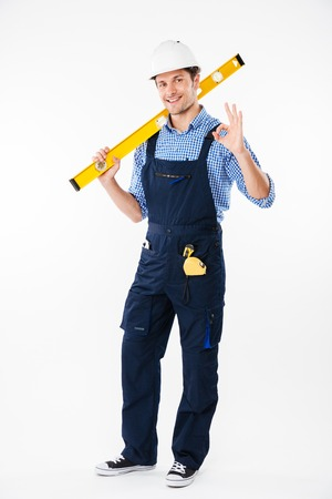 journeyman: Full length portrait of a smiling male builder standing and showing okay gesture isolated on a white background