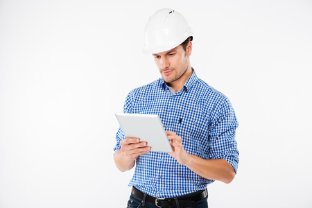 Serious young man architect in hard hat standing and using tablet