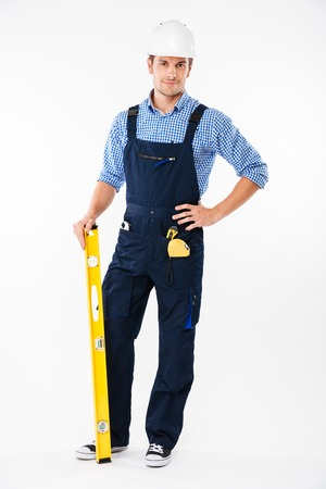 Full length portrait of a smiling male builder standing isolated on a white background Stock Photo