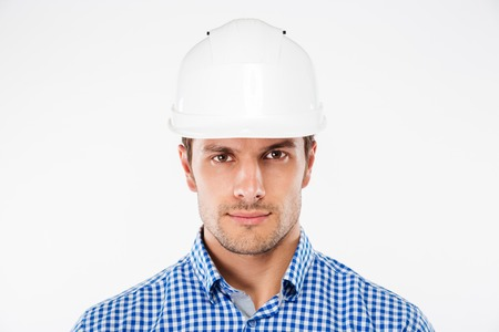 Portrait of serious young man architect in building helmet