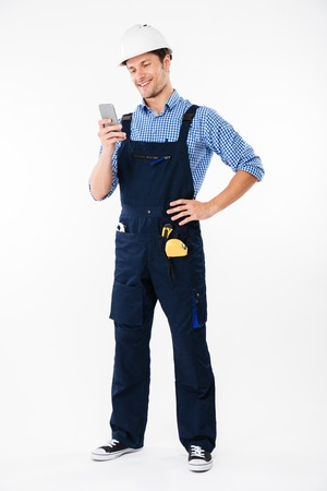 Full length portrait of a handsome male builder standing and using mobile phone isolated on a white background Stock Photo