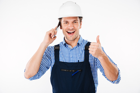 Happy young builder in overall talking on mobile phone and showing thumbs up gesture isolated on a white background