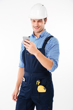 Portrait of a handsome male builder standing and using mobile phone isolated on a white background