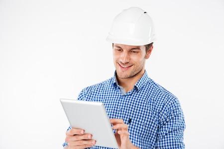 obrero trabajando: Ingeniero sonriente del edificio del hombre joven en el casco que usa la tableta Foto de archivo