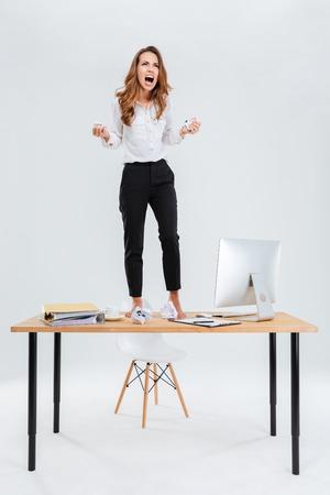 화가 미친 젊은 사업가 테이블에 서서 흰색 배경 위에 비명 스톡 콘텐츠