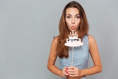 props: Pretty cute young woman blowing on birthday cake props over grey background