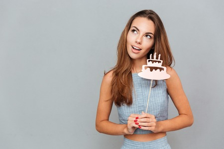 props: Happy lovely young woman holding birthday cake props over grey background