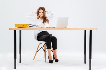 Confused embarrased young businesswoman working with laptop at the table over white background