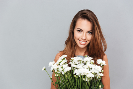 mujer con rosas: Closeup of cheerful attractive young woman with bunch of flowers over grey background Foto de archivo