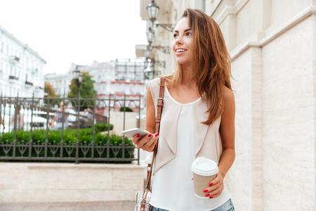 Smiling beautiful girl walking on the street and drinking take away coffee Stock Photo