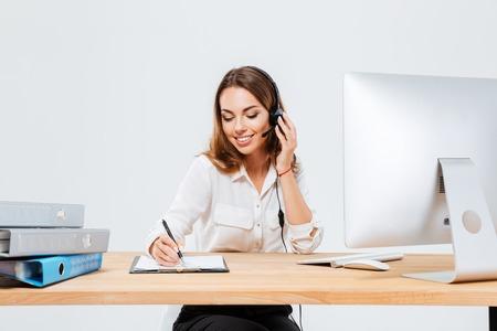 Sonriente joven haciendo notas mientras habla con custumer en el teléfono en el centro de llamadas sobre fondo blanco