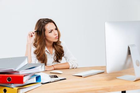 cabeza femenina: Concentrado pensativo negocios pensando en algo y rascándose la cabeza con la pluma isoltaed sobre el fondo blanco