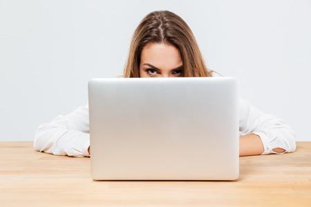흰색 배경 위에 그녀의 노트북 뒤에 숨어있는 젊은 갈색 머리 여자