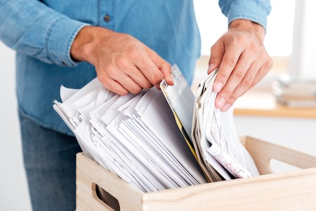 Close up portrait of man hands looking for documents in stack of folders on the office table Stock Photo