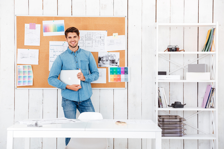 young man standing: Cheerful young man standing at the task board and holding laptop in office