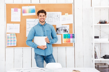 young man standing: Cheerful happy young man standing at the task board and holding laptop in office