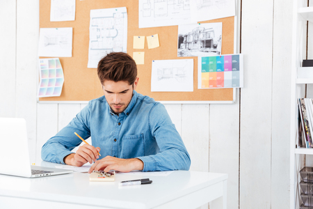 koncentrovaný: Concentrated young businessman sitting and writing at the table in office
