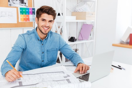 Handsome young businessman holding pencil and working with documents at the office