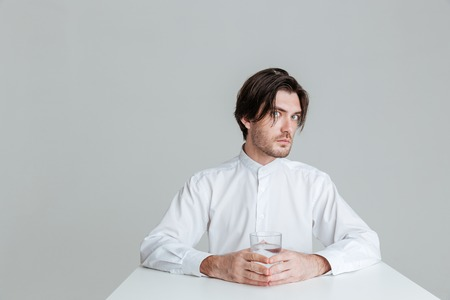 eyes wide open: Pensive brunette man with eyes wide open sitting at the table holding water glass isolated on the gray background Stock Photo