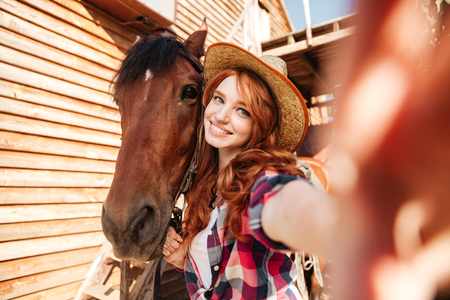 Cheerful lovely young woman cowgirl standing taking selfie with her horse on farm Reklamní fotografie