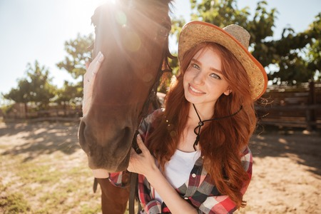 Happy smiling redhead young woman cowgirl with her horse in village Stock Photo