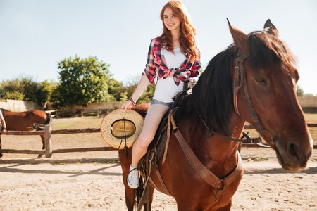 Smiling attrative young woman cowgirl riding horse in village Stock Photo