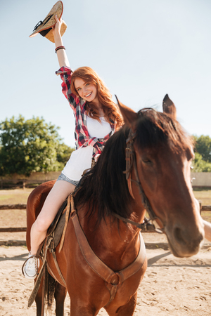Cheerful beautiful young woman cowgirl riding horse and having fun