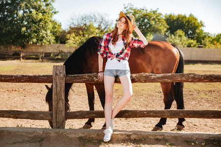 Full length of beautiful redhead young woman cowgirl staning with her horse on ranch