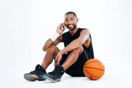Happy young man basketball player sitting and talking on cell phone over white background Stock Photo