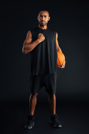 intense: Intense serious sports man with basket ball holding hand on his chest isolated on a black background Stock Photo