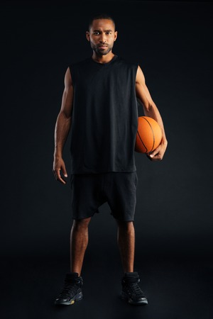 Concentrated serious african sports man holding basket ball and looking at camera isolated on a black background Stock Photo