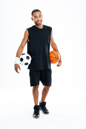 american sport: Cheerful african sports man holding basketball and soccer ball isolated on a white background