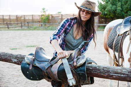 Beautiful young woman cowgirl in hat preparing saddle for riding horse Stock Photo