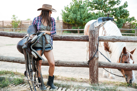 Happy beautiful young woman cowgirl in hat standing and holding saddle for riding horse