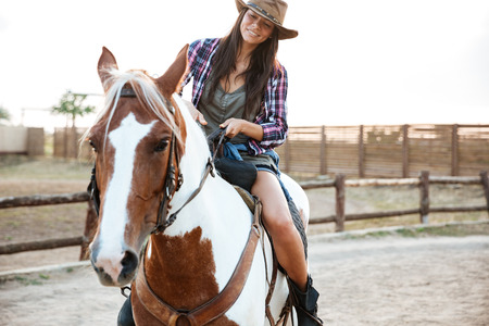 Smiling pretty young woman cowgirl riding a horse outdoors Stock Photo