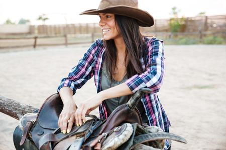 Porträt von fröhlichen Cowgirl junge Frau Sattel vorbereitet für Reiten