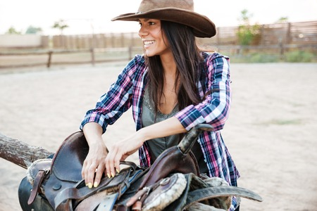 Portrait of cheerful young woman cowgirl preparing saddle for riding horse Stock Photo