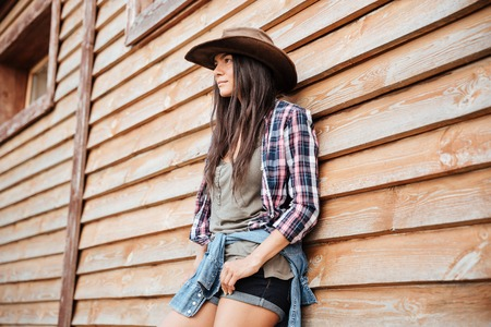 womna: Portrait of attractive young womna cowgirl in hat standing near the house