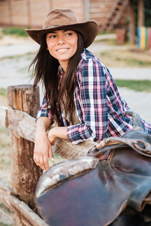 Smiling brunette young woman cowgirl leaning on fence in village and looking away Stock Photo