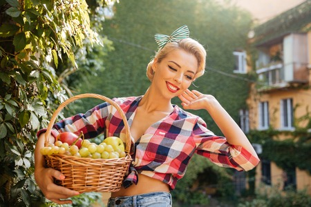 rich people: Happy beautiful pin up girl walking and holding basket of fresh fruits Stock Photo