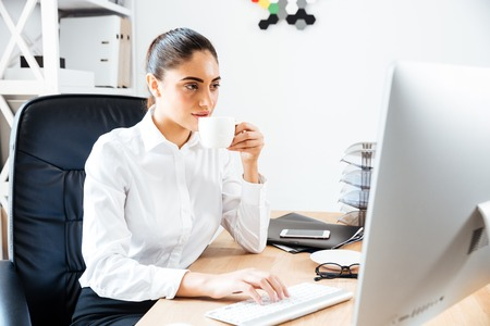 lovely businesswoman: Lovely young businesswoman using laptop and drinking cup of coffe while sitting at the office desk