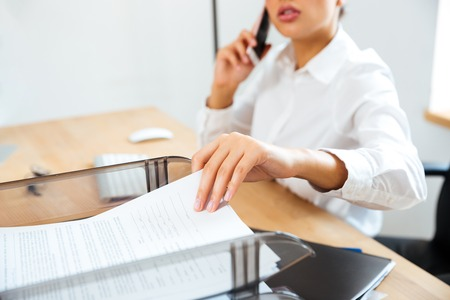 phone professional: Cropped image of young businesswoman talking on the phone and taking documents from the office table