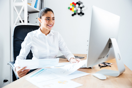 analytic: Smiling happy businesswoman holding reports and looking at computer while sitting at the workplace Stock Photo