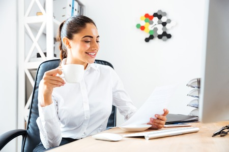 analytic: Lovely young businesswoman reading report and holding cup of coffe while sitting at the office desk Stock Photo