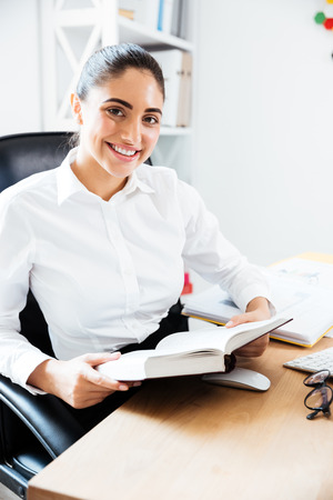 analytic: Attractive smiling businesswoman reading book while sitting at the workplace in office Stock Photo