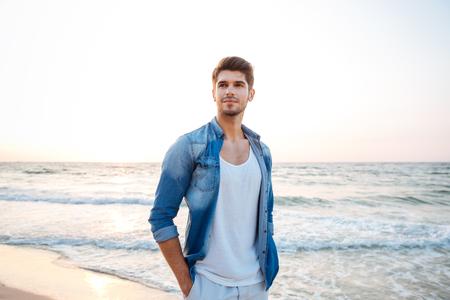 Beau jeune homme en jeans chemise debout sur la plage